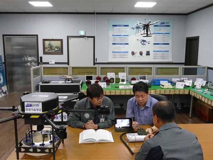 오병후(뒷줄 오른쪽) 창원기술정공 대표가 경남 창원시 회사 사무실에서 지뢰탐지 드론의 원리를 설명하는 모습. 창원기술정공 제공